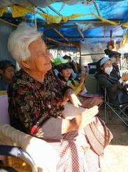 連日ゲート前に座り込みに参加している島袋文子さん。古謝美佐子さんの歌に手拍子をしているところ。右奥に糸数慶子参院議員と、語りと歌を披露した音楽家の海勢頭豊さんの姿も
