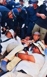 座り込む市民を排除する機動隊=22日午前7時、東村高江のN1地区出入り口(金城健太撮影)