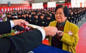 晴れやかな表情で卒業証書を受け取る國吉キク子さん=10日、那覇市立小禄中学校