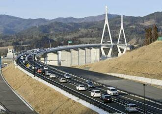 三陸沿岸道路を走行する車両。奥は気仙沼湾横断橋=6日午後、宮城県気仙沼市