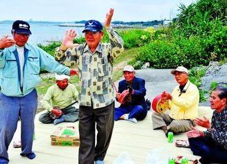 喜屋武集落の年中行事「ピーリンポーリン」で、三線とチジン(太鼓)の音に合わせて踊る男性たち=糸満市喜屋武の海岸