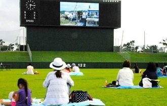 バックスクリーンに映し出された映画を鑑賞する人たち=8月30日、北谷公園野球場