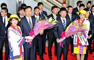 歓迎セレモニーで花束を受け取るヤクルトの小川淳司監督(左)と比屋根渉選手=那覇空港