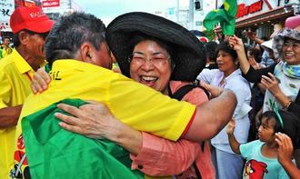 再開を喜び抱き合うパレード参加者と観客