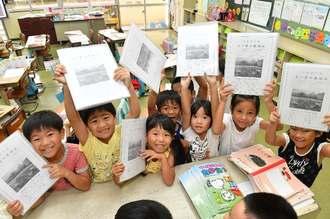 初めて渡された「よい子のあゆみ」を掲げて喜ぶ1年生の児童=4日午前、豊見城市・とよみ小学校