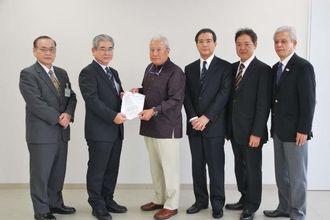兼次俊正部長(左から2人目)に要請書を渡した宮里一郎理事長(同3人目)ら=26日、那覇市役所