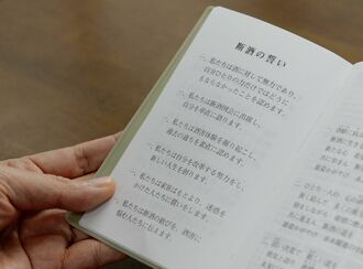 断酒会の手帳には「私たちは酒に対して無力」「過去の過ちを認めます」と書かれている=本島南部