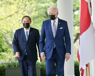 会談後、共同記者会見に向かう菅首相(左)とバイデン米大統領=16日、ワシントンのホワイトハウス(共同)