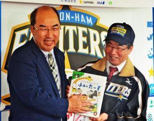 稲嶺市長(右)に絵本を贈る村田委員長=20日、名護市営球場