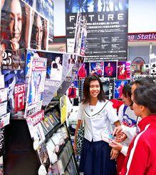 安室奈美恵さんの特設コーナー前で作品を手にする高校生たち=15日、サンエー那覇メインプレイス内「サウンドボックスミツトモ」