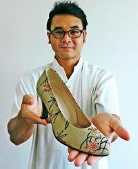 紅型の技術で染めた革靴をPRする安里紅型工房の安里昌敏さん=27日、沖縄タイムス社