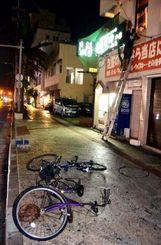 台風21号の接近による強風で倒れた自転車。後方では男性店員が看板に防風ネットを張る作業に追われた=27日午後9時すぎ、石垣市大川