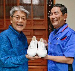 宮城勇さん(左)に復刻シューズを贈るアサヒシューズ沖縄支所の富松義彰主任