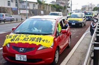 「爆音なくせ」などの横断幕を車に貼り付けて普天間飛行場周辺を走る自動車デモ=3日、宜野湾市の野嵩ゲート前