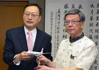 中国東方航空の飛行機模型を手に、福州―那覇の定期便就航を報告した李総領事(左)と翁長知事=15日、県庁