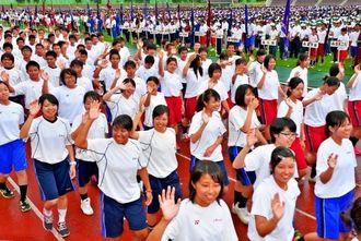 手を振りながら元気よく行進する選手たち=県総合運動公園陸上競技場(伊藤桃子撮影)