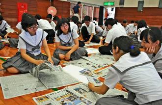 テーマごとに切り抜く記事を決め、意見交換する生徒=27日、南風原町・開邦高校
