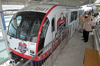 関係者に見送られ、那覇空港駅を出発する「日米野球ラッピングゆいレール」=6日午前