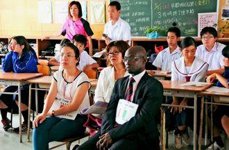 生徒らの説明を聞きながら沖縄戦の映像に見入る研修生ら=3日、糸満小学校