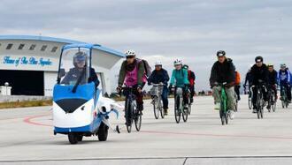 ブルーインパルスの機体を模したスクーターの先導で、航空自衛隊松島基地の滑走路をサイクリングする参加者=9日午前、宮城県東松島市