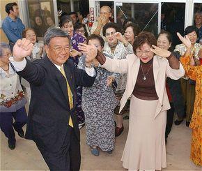 妻の樹子さん(右)や女性支持者らに囲まれてカチャーシーを踊る翁長雄志さん=2004年