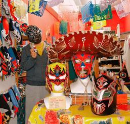 ルチャリブレのマスクや工芸品が並ぶ店内。普段は素顔で接客する与儀静香さんも「顔が新聞に出るといろいろ大変」とマスクをかぶった=那覇市牧志