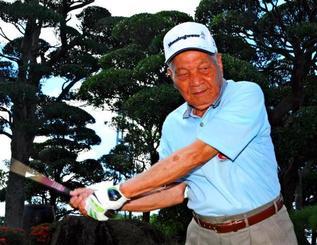 「数え年エージシュート」を95歳で達成した屋宜宣貞さん。得意のドライバーを振る=22日、八重瀬町の自宅