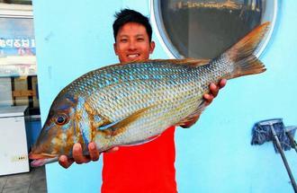 伊平屋島で62センチ、2.92キロのタマンを釣った照屋秀介さん=10月8日
