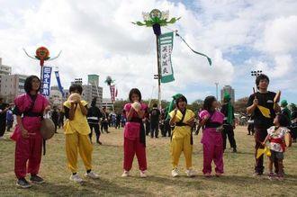 旗頭が掲げられた広場で、ホラ貝を吹く女の子たち=那覇市おもろまちの新都心公園