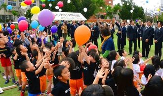 風船を空に舞い上げ、震災犠牲者を追悼する子どもたち=石垣市新栄町