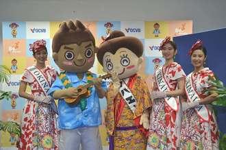 沖縄観光コンベンションビューローの新マスコットキャラクター「マハ朗くん」(左から2人目)の登場を喜ぶ「花笠マハエちゃん」(中央)=10日、那覇市の沖縄産業支援センター