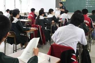 問題を受け取り、テストに臨む生徒たち=18日午前、那覇市立仲井真中学校