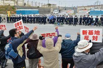キャンプ・シュワブのゲートを封鎖し、市民を排除する警察官に抗議する反対市民ら(手前)=16日午前8時30分、名護市辺野古