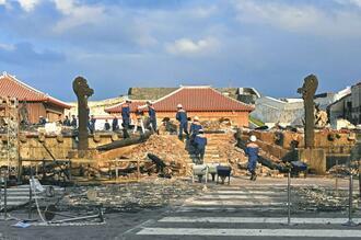 全焼した正殿で実況見分する消防職員と焼け残った龍柱2体。ネットで「奇跡の龍柱」と話題になっている=2日、那覇市首里当蔵町・首里城内