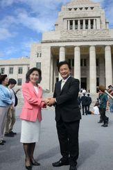 初登院し、院内会派を組む糸数慶子参院議員(左)と握手を交わす伊波洋一氏=1日午前、国会議事堂前