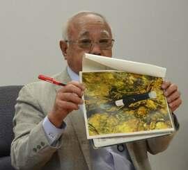 宮古島市で見つかった「ウランペレット」と表示された物体の写真を掲げる下地敏彦市長=19日午前9時すぎ、宮古島市役所