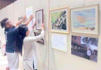 「正子・ロビンズ・サマーズ絵画展」の展示作業を行う実行委のメンバー=24日、那覇市久茂地・タイムスホール
