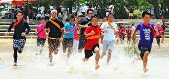 勢いよく水しぶきを上げて疾走する水中駅伝=12日、宮古島市下地・与那覇湾