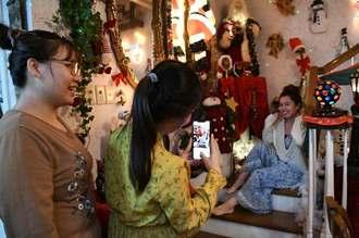 クリスマスグッズでいっぱいの店内では記念撮影するお客さんも多い=22日、うるま市石川の「夢見る天使」