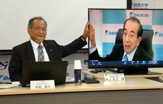 包括連携協定を結んだ鳥取大の中島広光学長(左)とリモートで記者会見に参加したダイキン工業の井上礼之会長=23日午後、鳥取市