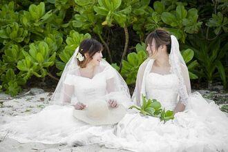 LGBTのカップルモデルとして、ウエディングドレス姿で撮影に臨む安里ミムさん(左)とみーちゃん=3月、石垣市(ONESTYLE提供)