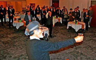 川満信一さんの音頭で献杯する岡留安則さんを偲ぶ会の参加者=26日、那覇市・県青年会館