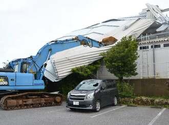 暴風ではがれたトタン屋根が飛散しないよう押さえる重機。駐車中の車はフロントガラスが割れていた=9日午前11時ごろ、宮古島市平良松原