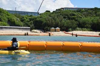 「K1」護岸予定地に設置されたフロート付近で、抗議するカヌーの市民(手前)と警戒する海上保安官(奥)=18日午前10時40分すぎ、名護市辺野古のキャンプ・シュワブ沖