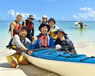シーカヤックに挑戦した三代達也さん(中央)とサポートした仲間たち=14日、今帰仁村・ビーチ「カネシバマ」