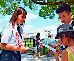 核兵器廃絶に向け署名活動をする沖縄尚学高校の稲福祈子さん(左)=5日、広島市の原爆ドーム前