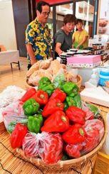 ピーマンなど新鮮な食材が並ぶ即売コーナーの準備に追われる出店業者=23日午後、那覇市久茂地・タイムスビル