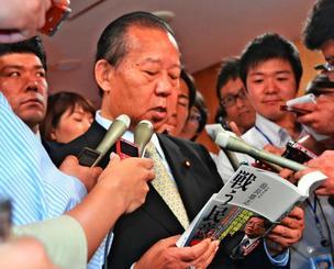 贈られた知事の著書を読む二階自民党幹事長(中央)=10日、東京・自民党本部