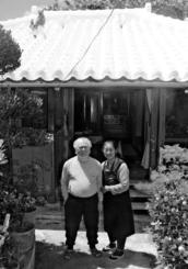 糸満売りで培った潜水技術が糸満一とされた島袋本一郎さんが、故郷・国頭村から糸満に移築した赤瓦の家。長男の勝男さん(72)(左)と昭子さん(67)夫妻が大切にしながら今も住んでいる=6月28日、糸満市糸満