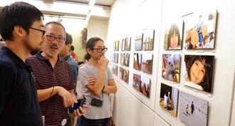 来間島の子どもたちの写真展「ぼくたちの場所」で作品に見入る来場者ら=1日、都内のギャラリー・アートグラフ
